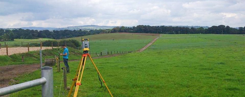 Members of the Vector Surveying team using a laser to map farm land.